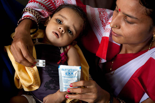 Anganwadi health worker Chaurasia Anita  with 8 month old Priyancu Kumari and some oral rehydration salts (ORS) and zinc tablets at the local clinic on the porch of her residence in Rajasan Village. The village located in Vaishali district outside Patna in Bihar, India has been rolling out the ORS and Zinc program as part of the Ikea Social Initiative to combat child mortality rates caused by diarrhea. It is proving to be very successful with education and support provided by local nursing staff, health activists  and program officers from UNICEF. The treatment is a 14 day course administering diluted oral rehydration salts and a zinc tablet which is more effective than salts alone in combating the effects of severe diarrhea. Picture by Graham Crouch/UNICEF