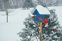Blue birdhouse with cardinals and wreaths in snow