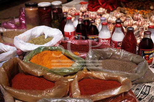 Sao Paulo, Brazil. Fresh spices (colorao, pimenta do reino, pimenta da malagueta), coconut milk, dende oil and peppers in oil.