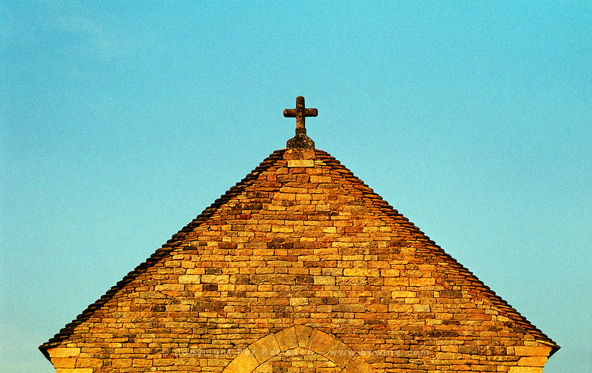 A small medieval chapel in the Burgundy village Salmaise at sunset: the roof and the cross