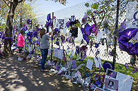 Woman photographing Prince memorabilia on the fence with purple balloons and flowers. Paisley Park  Chanhassen Minnesota MN USA