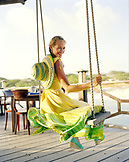 Aruba, Surfside Marina, a young woman sits on a swing smiling at Pinchos Bar & Grill