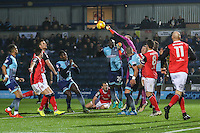 Goalkeeper Barry Roche of Morecambe clears the ball ahead of Adebayo Akinfenwa of Wycombe Wanderers during the Sky Bet League 2 match between Wycombe Wanderers and Morecambe at Adams Park, High Wycombe, England on 12 November 2016. Photo by David Horn.