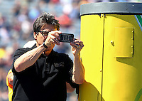 Sept. 21, 2013; Ennis, TX, USA: Texas governor Rick Perry takes pictures with his iPhone during NHRA qualifying for the Fall Nationals at the Texas Motorplex. Mandatory Credit: Mark J. Rebilas-
