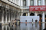 Tourists on flooded St Mark's square during an acqua alta (high-water). The Acqua Alta, a convergence of high tides and a strong sirocco, reached 125 centimetres in Venice, on November 20, 2013.  <br /> <br /> &copy; Pierre Teyssot