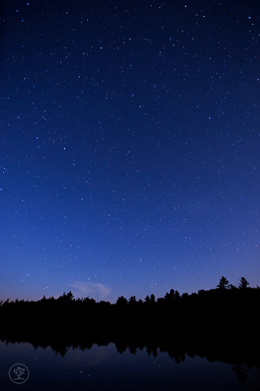 Stars shine in the blue hour above the still waters of Balsam Lake, Killarney Provincial Park, Ontario, Canada
