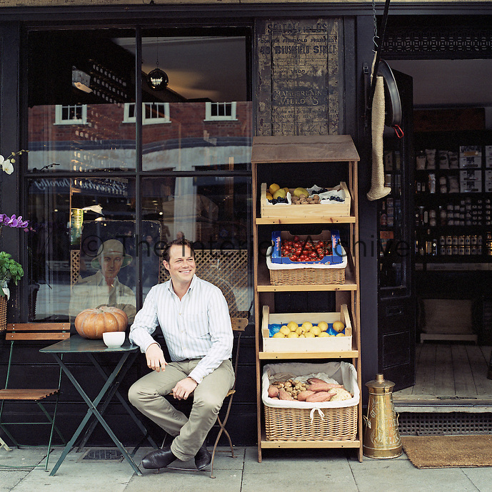 Portrait of interior and garden designer Malcolm James Kutner sitting outside his local cafe in Spitalfields, London