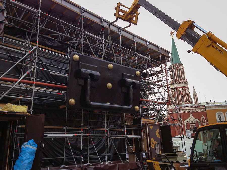 Moscow, Russia, 01/12/2013.<br /> Workers dismantle the handle of a giant 30 meter by 9 meter Louis Vuitton suitcase on Red Square. The two storey high suitcase, meant to host a Louis Vuitton display, caused outrage amongst politicians and public, and was ordered to be removed.
