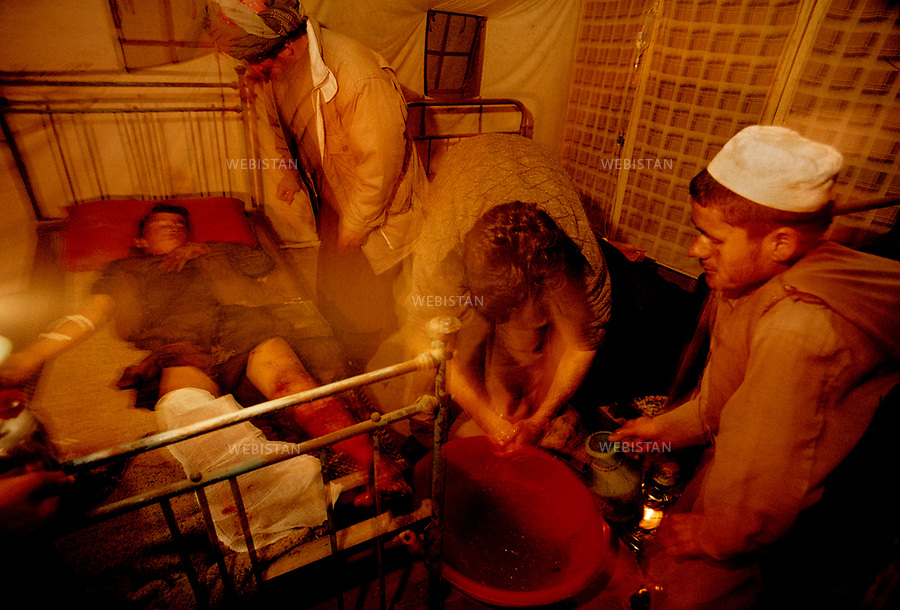 Afghanistan, Takhar, Dasht-e Qal'eh. November 27th, 2000.<br /> Picture taken at 21h00, west of the Kowkcheh River, opposite Ai Khanoum position. In this tent, used as a campaign hospital, Dr. Atigh and his assistants operate and tend men wounded by anti-personnel mines, as they were trying to reach Talibans' positions a few hours previously. &nbsp;<br /> <br /> <br /> Afghanistan. Takhar. Dasht-e-Ghala, &agrave; l'ouest de la rivi&egrave;re Kouktcha, en face de la position de A&iuml;-Khanoum. 27/11/2000.<br /> H&ocirc;pital de campagne install&eacute; sous une tente o&ugrave; le docteur Atigh et ses assistants donnent les premiers secours et op&egrave;rent les soldats bless&eacute;s par des mines anti-personnel dans leur ascension vers les positions taliban quelques heures plus t&ocirc;t.