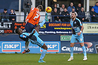 Aaron Pierre of Wycombe Wanderers gets the ball ahead of Alex Lawless of Luton Town while Paul Hayes of Wycombe Wanderers (right) looks on during the Sky Bet League 2 match between Luton Town and Wycombe Wanderers at Kenilworth Road, Luton, England on 26 December 2015. Photo by David Horn.