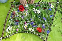 Kinder weben ein Blumenbild, Mädchen hat einen Rahmen aus Ästen gebaut, Wolle dazwischen gespannt und webt nun gesammelte Blumen ein