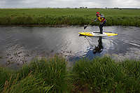 Rita Norvaisaite, tries stand-up paddling, SUP, during the bird festival in the Nemunas River Delta, Lithuania
