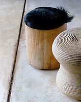 A pair of foot stools, one of which is covered in animal skin, on a polished cement floor