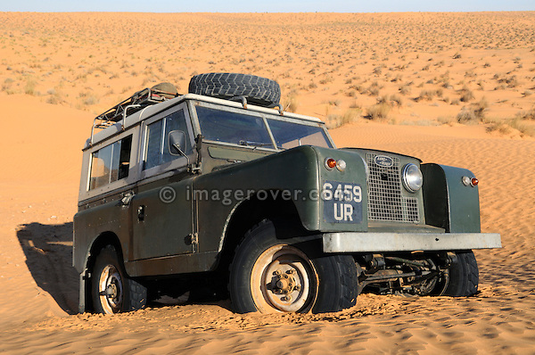 Africa, Tunisia, nr. Ksar Rhilane. Land Rover Series 2a stuck in sand dunes. --- No releases available, but releases may not be needed for certain uses. Automotive trademarks are the property of the trademark holder, authorization may be needed for some uses.