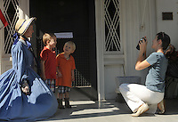 NWA Democrat-Gazette/ANDY SHUPE<br /> Lori Johnson (right) of Fayetteville takes a photograph Saturday, Aug. 15, 2015, of her sons, Walter Johnson, 4; (center left) and Charles Johnson, 2; with volunteer Judy Costello during the 44th annual Washington County Historical Society Ice Cream Social at Headquarters House in Fayetteville. The annual event featured music, ice cream, desserts and tours of the Civil War-era house and museum.