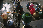 INDIA, Tamil Nadu, woman fills pots with drinking water from a tap which runs onetime a day only in a fishing village near Nagapattinam / INDIEN Frau füllt Trinkwasser in Krüge von einem Wasserhahn ab
