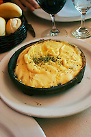 Regional dish of melted cheese on an iron plate with herbs, in the restaurant El Palenque, the sword fish swordfish, in the Mercado del Puerto, the market in the port harbour harbor where many people go and eat and shop on weekends Montevideo, Uruguay, South America