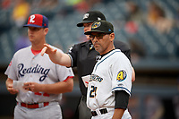 Rouglas Odor (24) during the lineup exchange with umpire Thomas Roche and Sean Williams (left) before an Eastern League game between the Reading Fightin Phils and Akron RubberDucks on June 4, 2019 at Canal Park in Akron, Ohio.  Akron defeated Reading 8-5.  (Mike Janes/Four Seam Images)