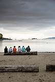 CANADA, Vancouver, British Columbia, friends sit by the waters edge at Sunset Beach, looking towards English Bay, Davie Village