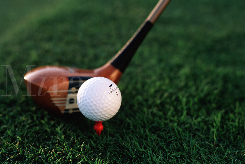 Detail of a driver lining up a shot against a golf ball on a tee.