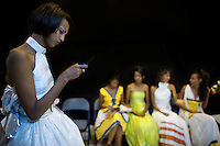 A contender for the crown writes a text message on her phone while others wait during the 2009 Miss Ethiopia beauty pageant held at the Intercontinental Hotel in Ethiopia's Capital Addis Ababa on Sunday January 18 2009.