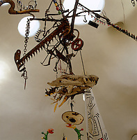 Detail of a sculptural machine by Jean Tinguely hanging from the ceiling of Niki de Saint Phalle's sculptural house