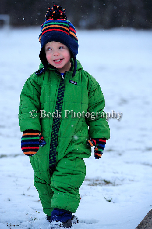 BOY IN THE WINTER SNOW PLAYING