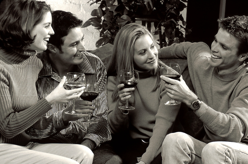 Smiling young couples relaxing and drinking wine.