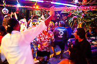 Party scene with visitors dancing with Tahitians