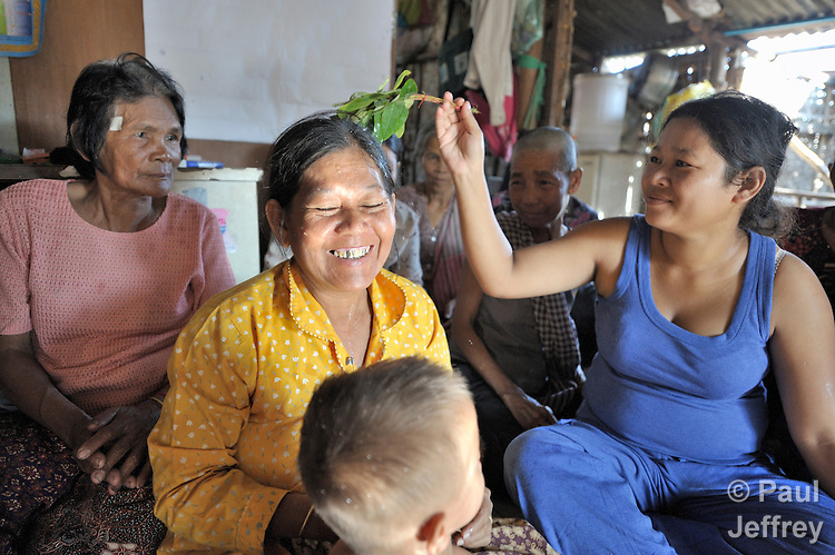 Chaum Siem blesses Chet Phan with water blessed by a Buddhist monk. The women are members of a self-help group in the Phnom Penh neighborhood of Sen Rikreay. Many people in this community are infected or affected by HIV and AIDS, and Buddhist monks and other religious meet with them regularly to mediate and discuss their challenges.