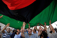 People celebrate at Martyrs' Square in Tripoli underneath a large flag. After a six month revolution, rebel forces finally managed to break into Tripoli and have taken control of Bab al-Aziziyah, Col Gaddafi's compound and residence. Few remain that are loyal to Gaddafi in the city; it is seeming that the 42 year regime has come to an end. Gaddafi is currently on the run.
