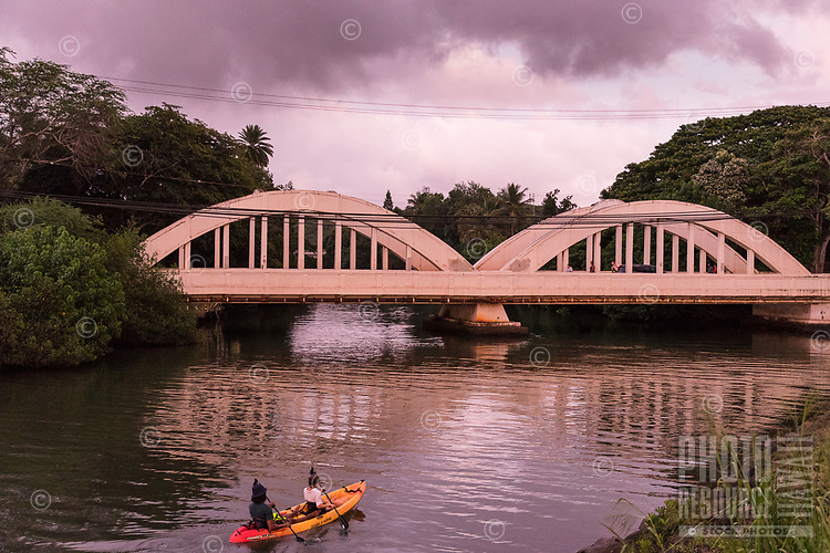 At sunset, a couple in a kayak paddle towards the historic Anahulu Bridge (a.k.a. Rainbow Bridge), Hale'iwa, North Shore, O'ahu.