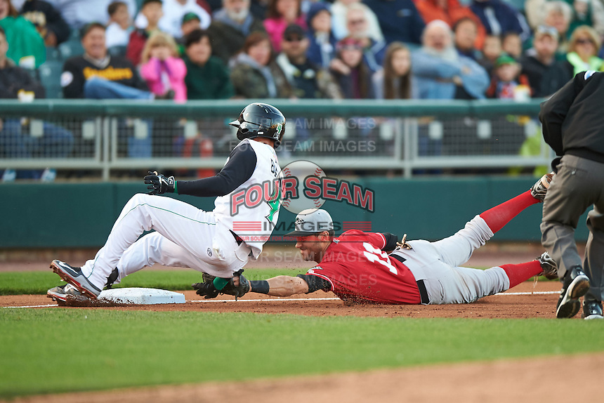 Great Lakes Loons third baseman Mike Ahmed (11) dives to tag Ronald Bueno (4) on the hand during a game against the Dayton Dragons on May 21, 2015 at Fifth Third Field in Dayton, Ohio.  Bueno was called safe as the Great Lakes defeated Dayton 4-3.  (Mike Janes/Four Seam Images)