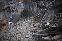 An elder man removes rubble from the street. Shanku near Kathmandu, Nepal. May 9, 2015
