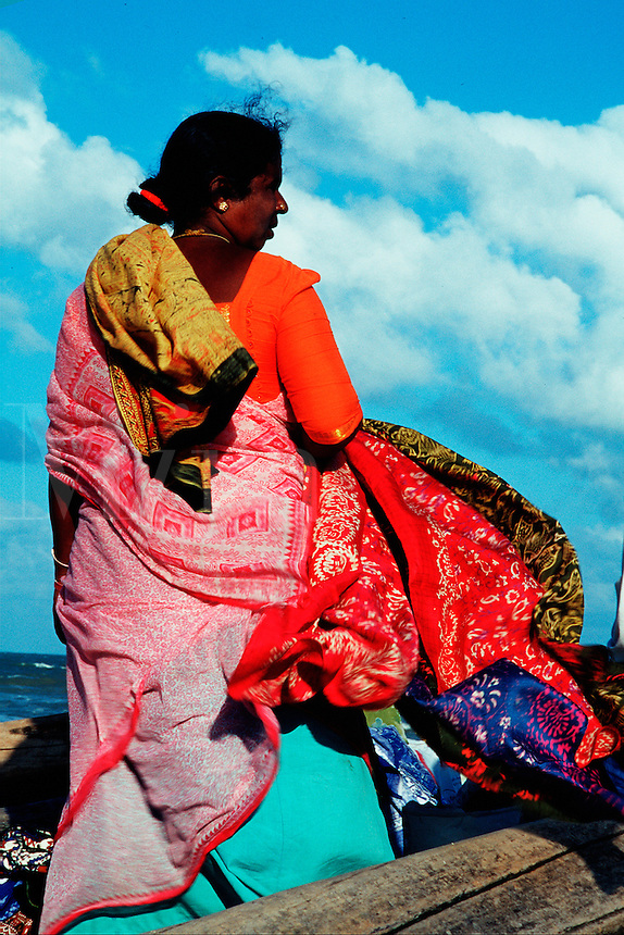 An Indian womain wears a colorful sari that blows in the breeze. Mamalap, India.