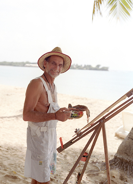 French Painter Marcel Tronet paints a water color painting on the beach at (Plage des Salines) ,Ste-Anne. Martinique. Caribbean.