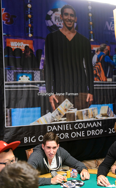 Dan Colman playing beneath his One Drop winner photo from 2014