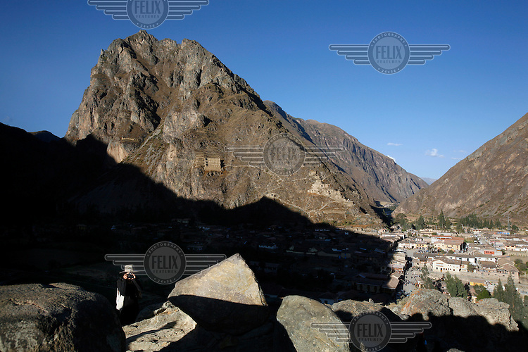 A girl takes a photograph at one of the Inca archaeological sites at Ollantaytambo. On the mountainside in the background is an Inca grain storage building.