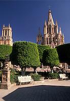 AJ1909, Mexico, San Miguel de Allende, Indian laurel trees shade the Central Plaza in San Miguel de Allende in the state of Guanajuato. Parich Church (La Parroquia) is seen in the background.
