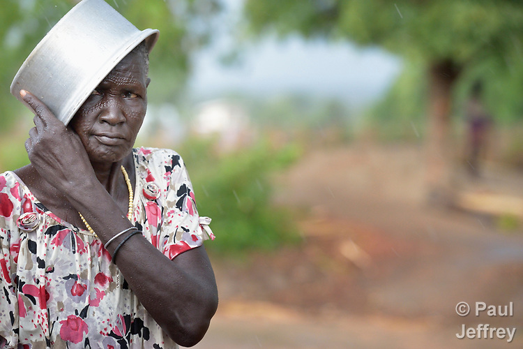 A woman uses a cooking pot to shield herself from the rain in the Rhino Refugee Camp in northern Uganda. As of April 2017, the camp held almost 87,000 refugees from South Sudan, and more people were arriving daily. About 1.8 million people have fled South Sudan since civil war broke out there at the end of 2013. About 900,000 have sought refuge in Uganda.