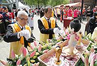 Nederland  Amsterdam  2016.  Boeddhadag op de Nieuwmarkt in Amsterdam. Viering van de geboorte van Boeddha. Alle aanwezigen schenken water over een kleine Boeddha figuur. Foto Berlinda van Dam / Hollandse Hoogte
