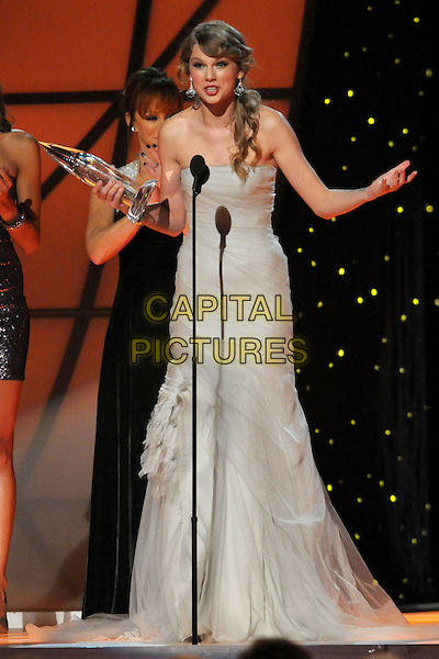 Taylor Swift.The 45th Annual CMA Awards, Country Music's Biggest Night, held at Bridgestone Arena, Nashville, Tennessee, USA..November 9th, 2011.on stage full length grey gray strapless dress award trophy winner tulle arm hands.CAP/ADM/LF.©Laura Farr/AdMedia/Capital Pictures.