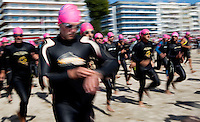 19 SEP 2010 - LA BAULE, FRA - A competitor starts his timer as he runs into the water at the beginning of the Triathlon Courte Distance - 23rd Triathlon Audencia-La Baule (PHOTO (C) NIGEL FARROW)