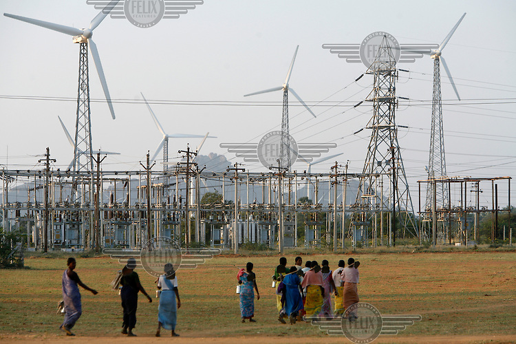 Women on their way to their daily chores walk past wind turbines at Muppandal wind farm. Muppandal is one of the largest wind farms in Asia.