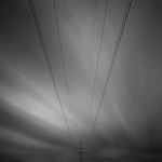 Eight electricity cables leading to a electricity pylon with a strange dramatic black and white sky behind