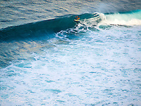 A woman surfer rides a wave at Honolua Bay, Maui.