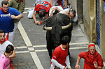 People run in front of Garciagrande´s fighting bulls during the fourth bull run in the San Fermin Festival on July 10, 2014, in Pamplona, Basque Country. Every year, tens of thousands of people pack Pamplona's streets for a drunken kick-off to one os worls's best-known fiesta: the nine-day San Fermin bull-running festival. (Ander Gillenea / Bostok Photo)