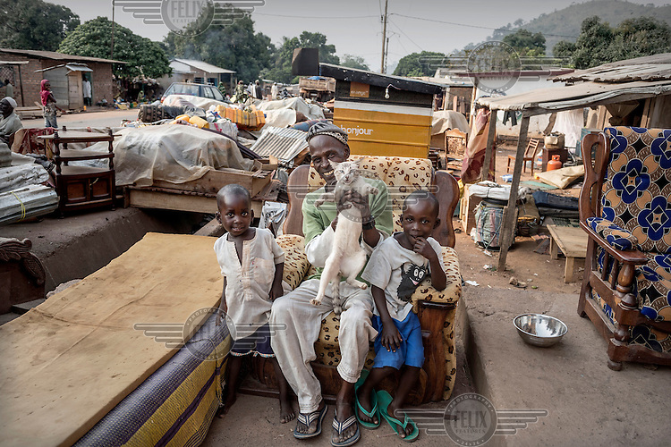 A man, his sons, their pet cat and their belongings wait, with other residents, to be evacuated from a Muslim district of the capital where they are surrounded by potentially hostile Christian neighbours. They have been under the protection of the French army while they wait. In 2013 a rebellion by a predominantly Muslim rebel group Seleka, led by Michel Djotodia, toppled the government of President Francios Bozize. Djotodia declared that Seleka would be disbanded but as law and order collapsed the Seleka roamed the country committing atrocities against the civilian population. In response a vigillante group, calling themselves Anti-Balaka (Anti-Machete), sought to defend their lives and property but they then began to take reprisals against the Muslim population and the conflict became increasingly sectarian. French and Chadian peacekeeping forces have struggled to contain the situation and the smaller Muslim population began to flee the country.