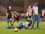 Stefan Scougall of Sheffield United in the air after a challenge from Leon Barnett of Bury during the English Football League One match at Bramall Lane, Sheffield. Picture date: November 22nd, 2016. Pic Jamie Tyerman/Sportimage