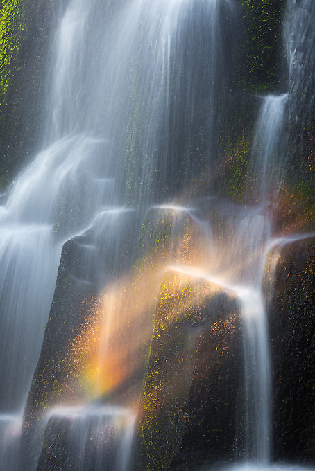 Soft light creating a rainbow across a cascading falls in the Cascade range of Oregon.